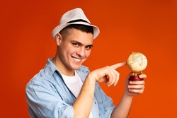 New destination to travel. Happy guy tourist pointing at globe in his hand, orange studio background