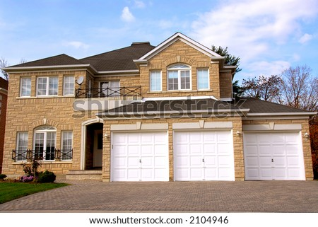 New detached single family luxury home with stone facade and triple garage