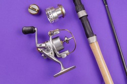 New Disassembled fly fishing reel and fishing rod on blue background. Metal bobbin without fishing line. Selective focus.