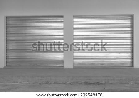 New Double Garage Doors Vintage\ New double sheet metal garage doors installed into  building in black white vintage.