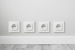 New electrical socket isolated on gray wall. Renovated studio apartment power supply background. Gray wooden floor. Empty copy space white plastic power outlet. Four sockets in a row.