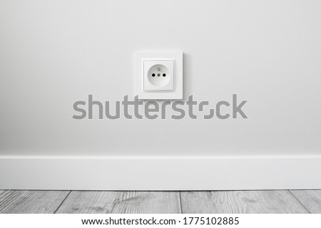 New electrical socket isolated on gray wall. Renovated studio apartment power supply background. Gray wooden floor. Empty copy space white plastic power outlet. Сток-фото ©