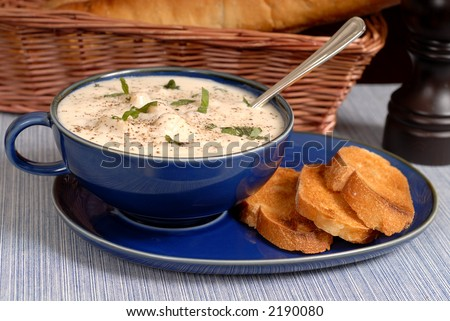New England Clam Chowder in a blue bowl with crostini