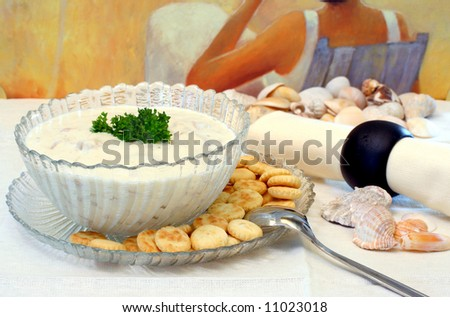 New England Clam Chowder in a glass bowl with condiments in a shore type setting.