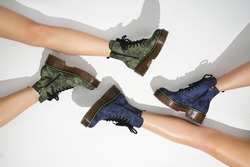 new fashion collection of footwear autumn winter 20/21 on the feet of models boots in the style of a military on a colored background fashion photos of shoes