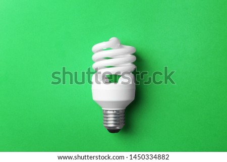New fluorescent lamp bulb on green background, top view