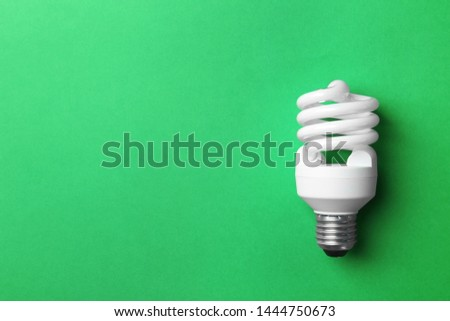New fluorescent lamp bulb on green background, top view. Space for text