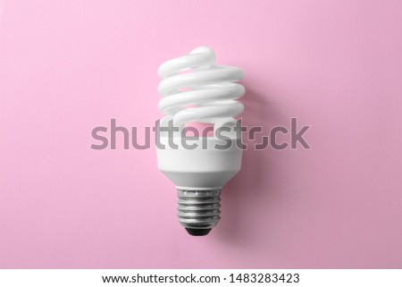 New fluorescent lamp bulb on pink background, top view
