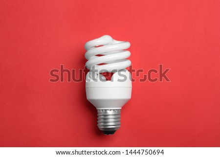 New fluorescent lamp bulb on red background, top view