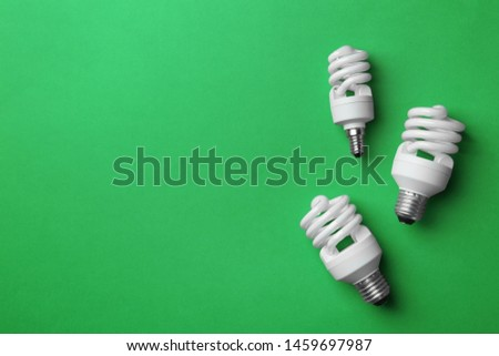 New fluorescent lamp bulbs on green background, top view. Space for text