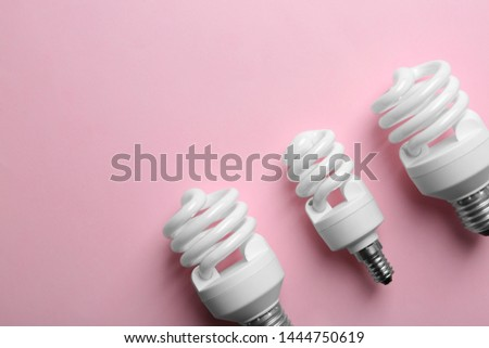New fluorescent lamp bulbs on pink background, top view. Space for text