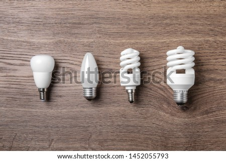 New fluorescent lamp bulbs on wooden background, flat lay