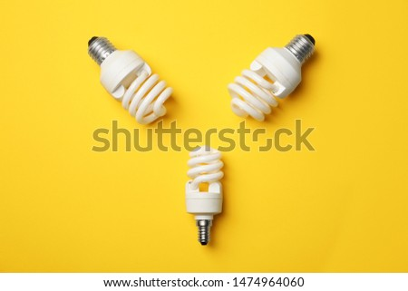 New fluorescent lamp bulbs on yellow background, top view