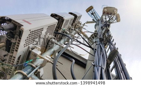 New 5G radio network telecommunication equipment with radio modules and smart antennas mounted on a metal tower radiating strong signal waves over the dense urban city from the roof of the building  #1398941498