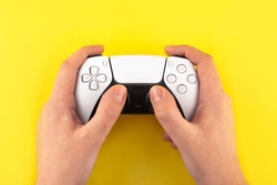 new gen joystick gamepad, game console on yellow colorful trendy modern background in man hands.