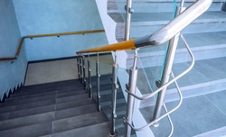 New glass staircase with railing. Modern design, stainless steel, glass and wood are applied when installing fall protection-railing on the stairs.