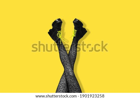 New gray female boots with bright yellow laces on long slender crossed woman legs in gray tights isolated on yellow background. Pop art concept with Heavy Duty Boots. Banner with copy space. Stock photo ©