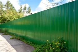 New green metallic fence in village