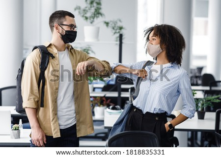 New greeting to avoid spread of coronavirus. Guy and african american lady in protective masks hello with elbows in morning in interior of coworking office, free space, indoors