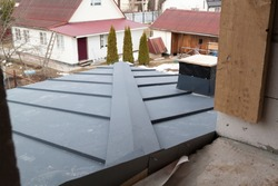 new grey folded metal roof of modern cottage viewed from above