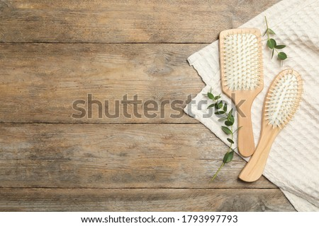 New hair brushes, twigs and towel on wooden background, flat lay. Space for text Foto stock ©