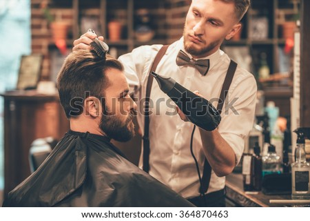 New hairstyle. Side view of young bearded man getting groomed at hairdresser with hair dryer while sitting in chair at barbershop