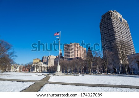New Haven Green with snow and blue sky: a park in downtown New Haven, CT used for public events and bordered by Yale University.