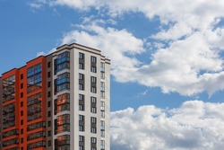 new high rise apartament building with multiple balcony and windows on blue sky with white clouds background