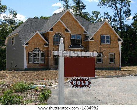 """New home being constructed with blank realtor sign and """"sold"""" plaque"""
