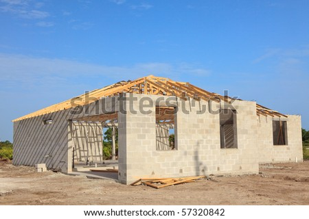 New home Construction of a cement block home with wooden roof trusses view from outside.
