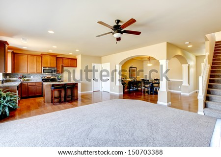 New home kitchen interior and large empty living room.