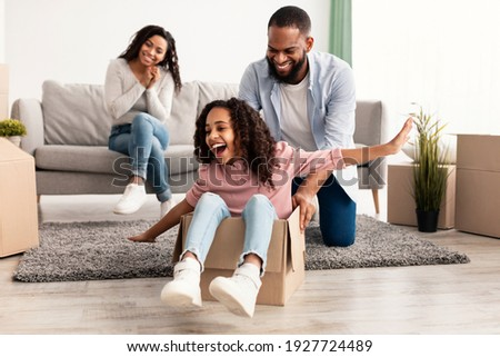 New Home, People And Real Estate Concept. Excited African American family having fun and celebrating moving day, cheerful father riding his little daughter in cardboard box container in living room Photo stock ©
