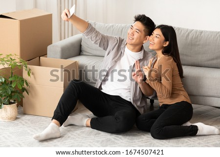 New Home, Technology Concept. Happy asian couple taking selfie with smartphone sitting on floor among cardboard boxes Foto stock ©