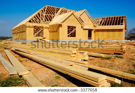 New home under construction with wood, trusses and supplies