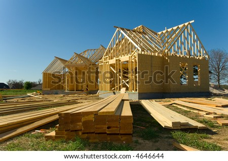 New home under construction with wood, trusses and supplies against blue sky