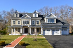 New house, colonial style, frontal view. Brick entrance walkway, paved driveway, landscaped garden.