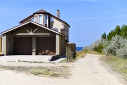 New house with garage doors and bay window on the Mediterranean coast. Sea horizon. Deciduous trees. Road to the sea.
