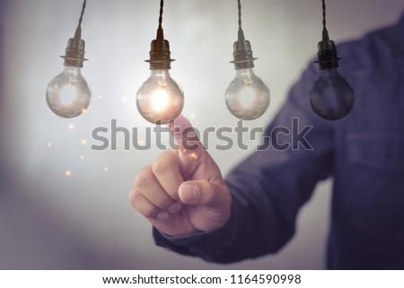 new idea creative idea.Concept of idea and innovation.Hand touch Light blub #1164590998