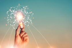 New ideas and imagination Creativity and inspiration Technological innovation. Hand holding brain digital network and abstract science light bulb inside on networking connection on sky background.