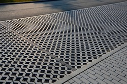 new infiltration parking lot made of porous concrete tiles in a regular square grid with holes filled with gravel. in connection with the asphalt road and the sidewalk with interlocking paving