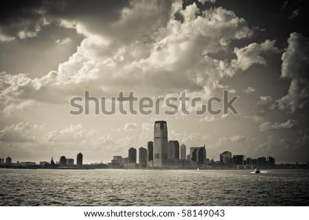 New Jersey city skyline under blue cloudy sky, vintage monochrome - stock photo