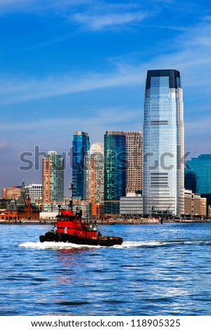 New Jersey skyline and waterfront viewed from the Hudson River with a red tugboat in the foreground. The city is Hoboken, across the water from lower Manhattan.