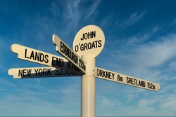 New John O'Groats signpost with blue sky and light cloud background. Caithness, Scotland, NC500 route.