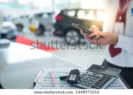 New key - Car showroom image with calculator and two new remote keys placed on the desk in a new car showroom. The background is a car showroom with a car salesman standing holding the phone.