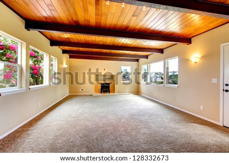 Large empty living room with wood ceiling and fireplace stock photo