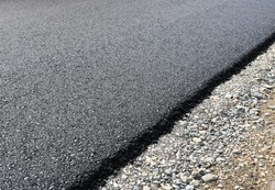 New layer of asphalt road under construction  with support from the European Union structural funds.