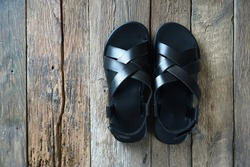 New leather men's sandals on the wooden floor. Top view. Copy space.