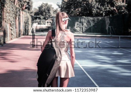 New lesson. Determined female player entering court and carrying tennis equipment #1172353987