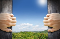 New life concept. 2 hands trying open a wooden door to new world.