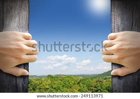 Shutterstock New life concept. 2 hands trying open a wooden door to new world.